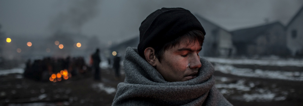 Hazrat, 16, an Afghan refugee, warms himself at a fire behind the main train station of Belgrade.  ©UNHCR/Daniel Etter