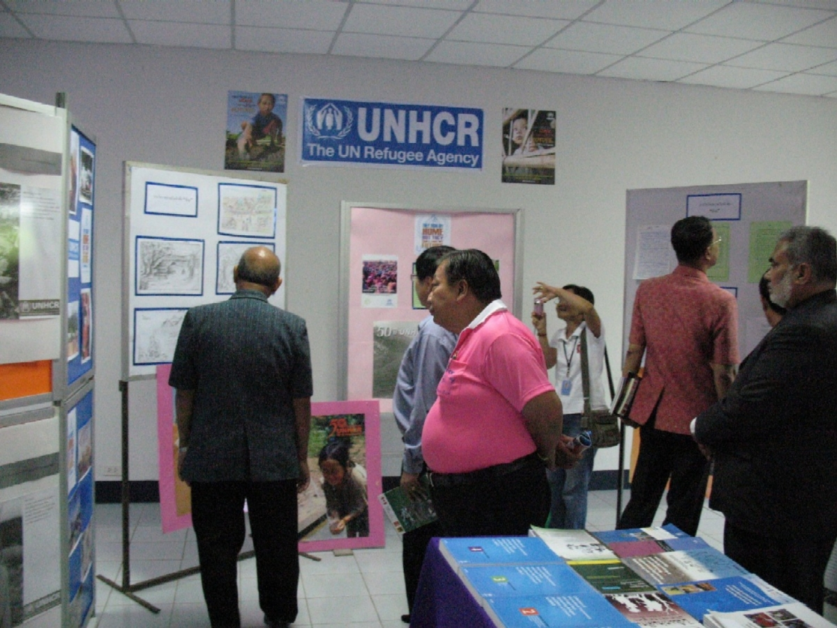 The Mae Hong Son Vice-Governor, District Officer, Representative from Chamber of Commerce and guests view exhibition in UNHCR's booth at the Community College on 22 June