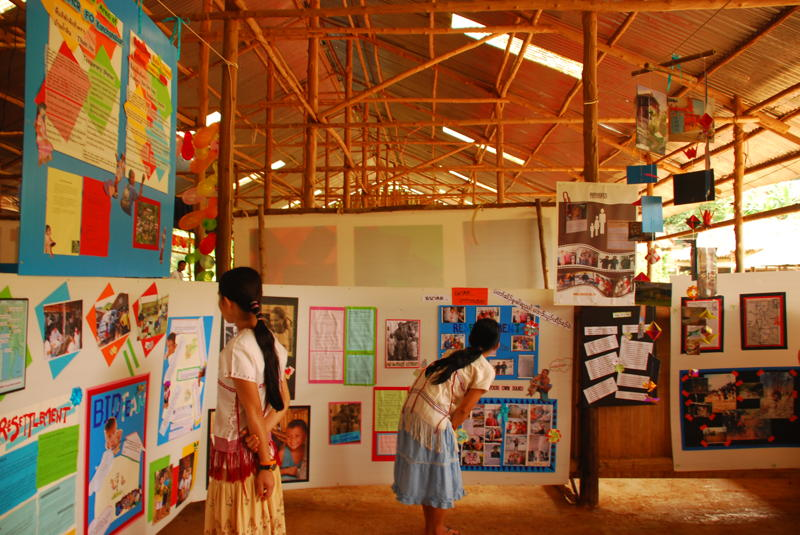 Refugee children learn about child protection from UNHCR exhibition.