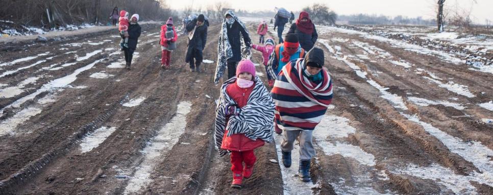 กลุ่มผู้ลี้ภัยใช้ผ้าห่มและเสื้อผ้ากันหนาวห่มตัวขณะลี้ภัยข้ามชายแดนมาซิโดเนีย-เซอร์เบีย ท่ามกลางอากาศที่หนาวจัดของเดือนมกราคม 2559