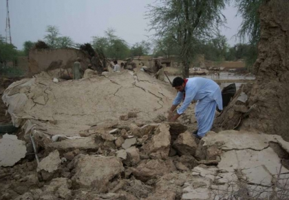 A man in Balochistan digs through the rubble in search of personal belongings to