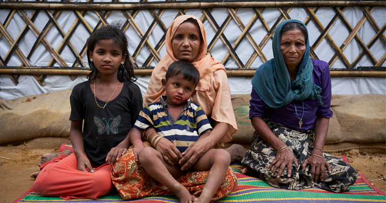 From left, Nur Kalima, 10, her mother Khadija, 40, brother Saiful Hoque, 4, and grandmother Suvia Khatun, 60, pose for a photograph as they sit outside their shelter. ©UNHCR/David Azia