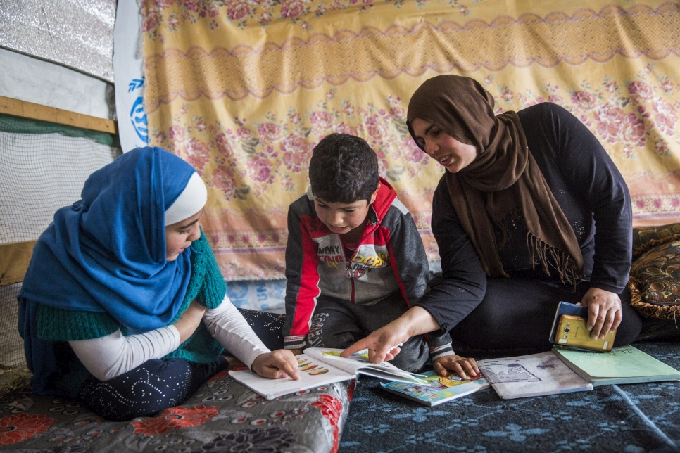 Abdulhay does homework in his family's shelter, joined by his sister Shahed, 12, and their mother, Rana, 37. The siblings attend a second-shift school in the afternoons.  © UNHCR/Andrew McConnell