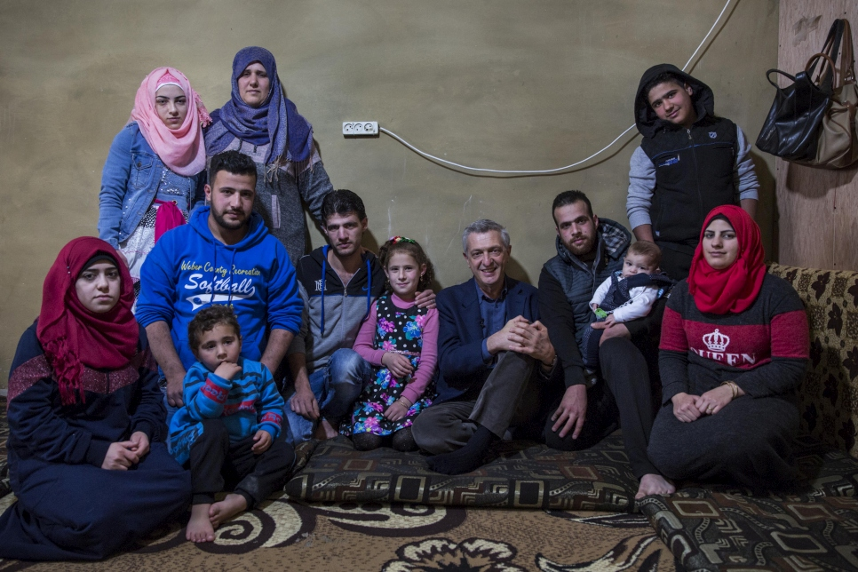 Wafaa (standing second left) and her family pose for a photo with UN High Commissioner for Refugees Filippo Grandi at their home in Zouq Bhannine, in northern Lebanon.  © UNHCR/Andrew McConnell