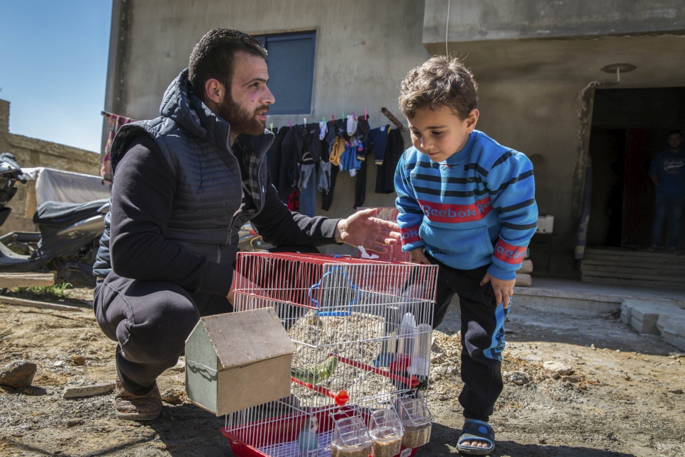Talal, 25, and his son Ahmed, 3, look at some of their pet birds outside the unfinished house where they are living in Zouq Bhannine, in northern Lebanon.  © UNHCR/Andrew McConnell