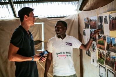 21 Year-old refugee Samson from Sudan's South Kordofan shows UNHCR High Profile Supporter Jung Woo-sung some of the photos and stories that he has written to highlight the situation of his people. Samson is a teacher in South Sudan's Ajuong Thok refugee camp and dreams of becoming a journalist. ©UNHCR/R. Nuri