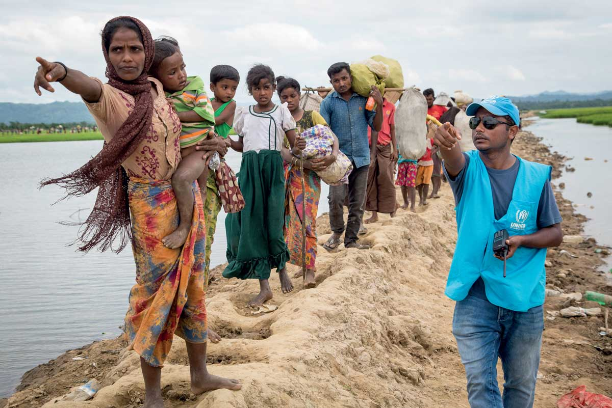 Rohingya family at Bangladesh border under assistance by UNHCR staff.