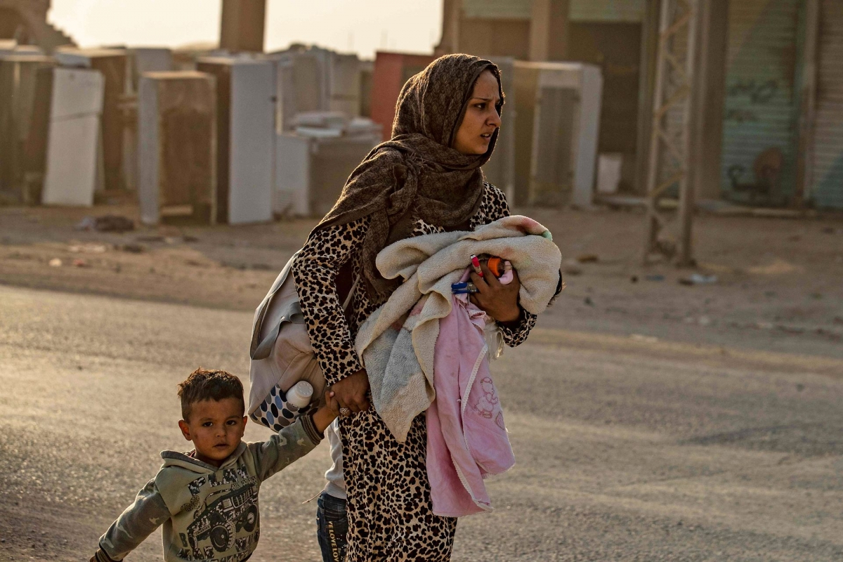 A woman flees with her children amid Turkish bombardment on Syria's northeastern town of Ras al-Ain in the Hasakeh province along the Turkish border on October 9, 2019. © Ritzau Scanpix