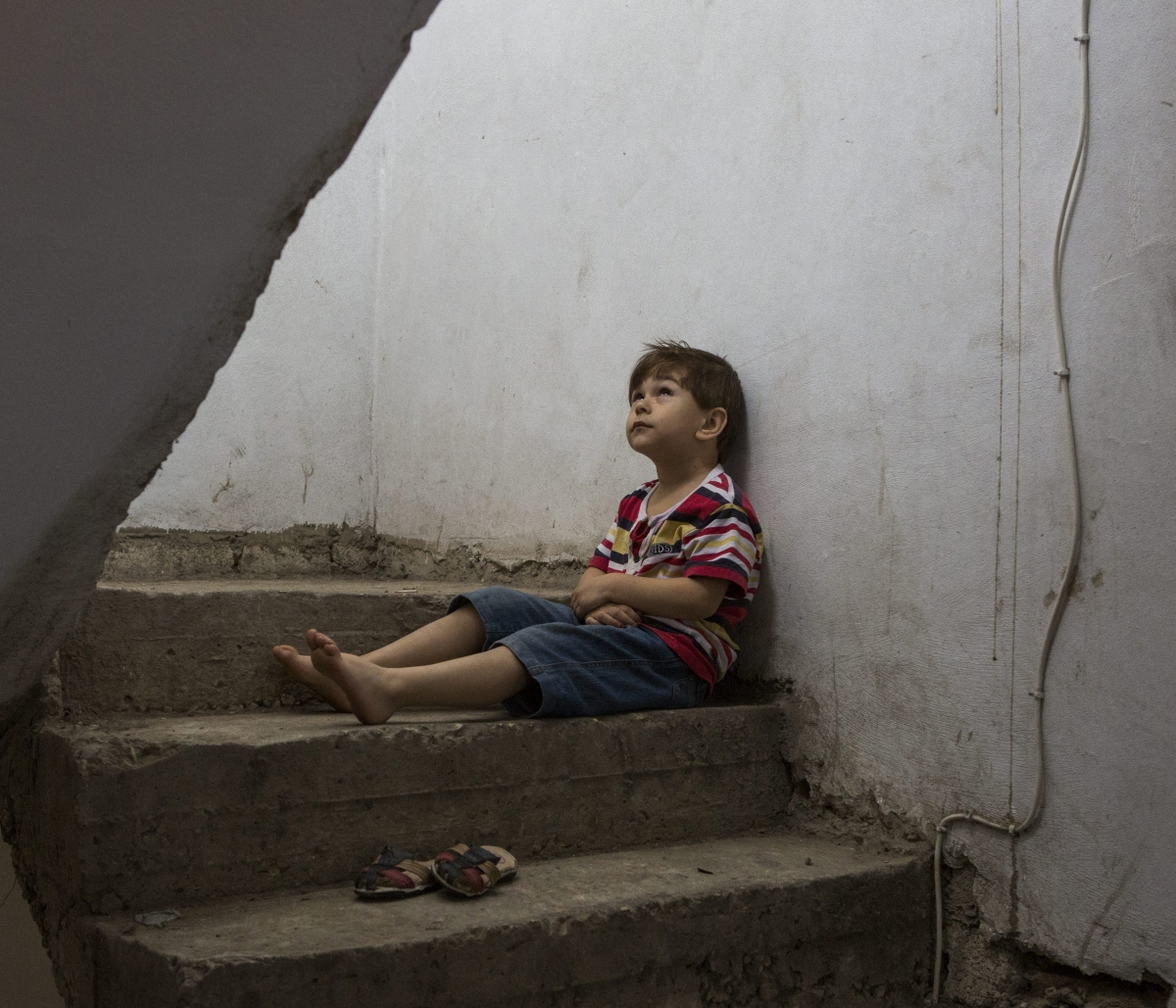 Omar, 8, sits in the stairwell of the building where he and his family have been living as refugees in Lebanon. © UNHCR/Ivor Prickett