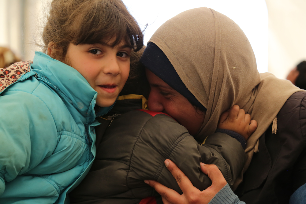 Hanan, an art teacher from Syria, embraces her two youngest children in a tent at the Italian port of Augusta, Sicily. Their search for safety included eight days on a deadly sea. ©UNHCR/F. Malavolta