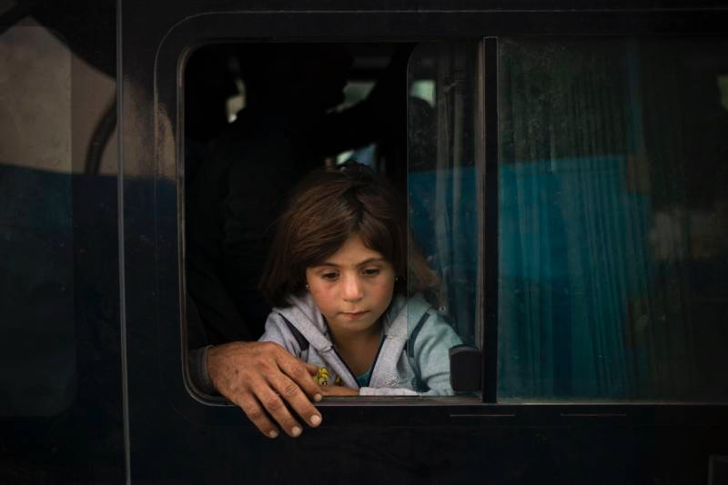 A young Syrian girl from Kobani and her father arriving at the Ibrahim Khalil Border Crossing in Iraq, after traveling by bus from Turkey. UNHCR / D. Nahr
