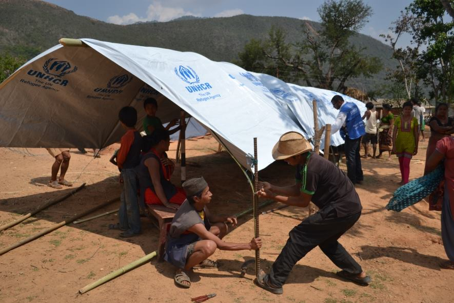 UNHCR staffs and Nepalis help install temporary shelter for survivors by using plastic sheets ©UNHCR