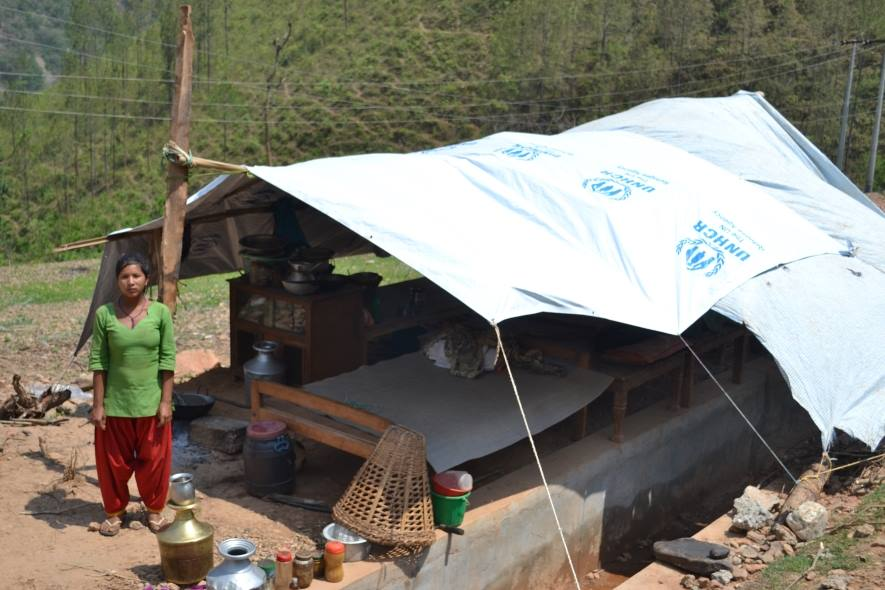 Earthquake survivor and temporary shelter to prevent her from rain and sunlight ©UNHCR