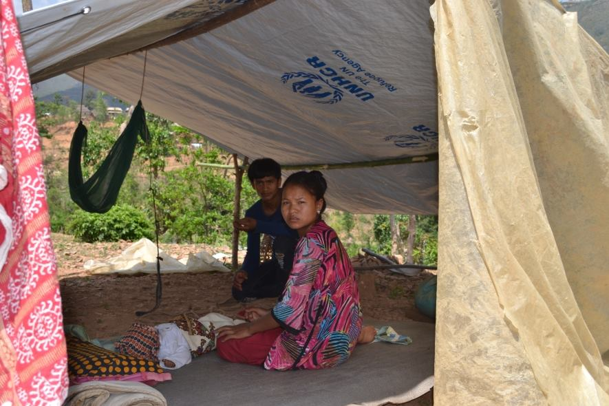 Survivor family and their temporary shelter made by UNHCR plastic sheets ©UNHCR