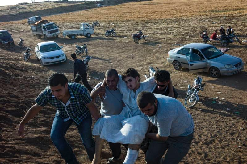 Syrian civilians carry a wounded Syrian man after he arrives at the Jordanian border. UNHCR / O.Laban-Mattei