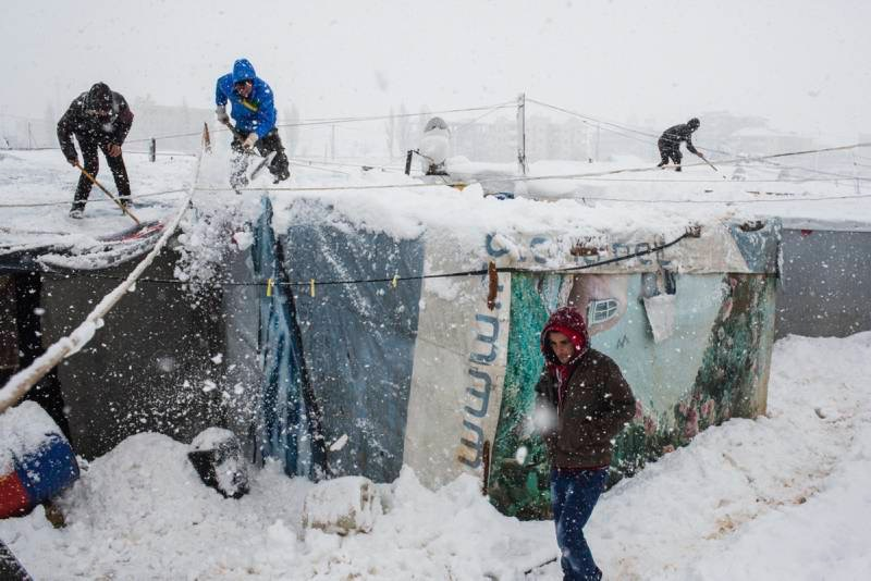 Syrian refugees remove snow from their shelters at an informal tented settlement in the Bekaa Valley, Lebanon. Winter storm 'Zina' swept through the region in January 2015, bringing snow and harsh conditions to millions of refugees. UNHCR / A. McConnell